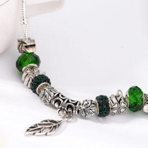 Zelený náramok s lístkom a rôznymi ozdobami
